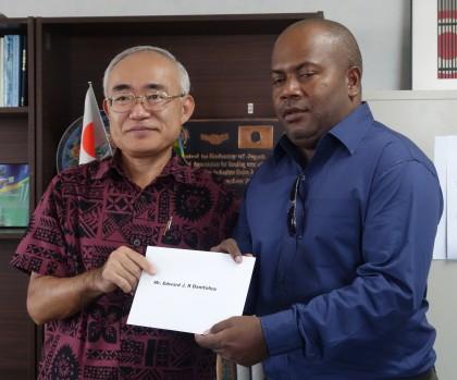 Edward Danitofea receiving his ticket from Japanese Ambassador Satoshi Nakajima. Photo: SIBC.
