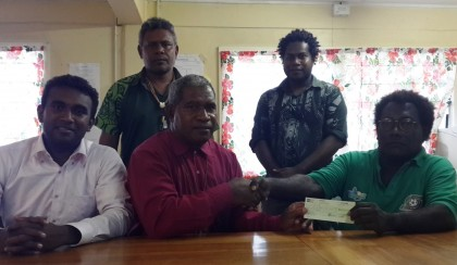 Bishop Lonsdale Hoamana hands of the cheque to Aseri Yalangono of the NDMO in the presence off Church and NDMO official. Photo credit: NDMO.