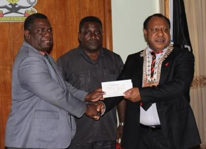 Environment Minister Bradley Tovosia recieves disaster grant from PNG foreign minister as PM Lilo looks on. Photo credit: OPMC.