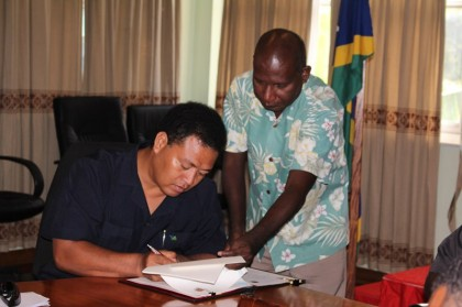 Foreign Affairs Minister Clay Forau signs the education agreement assisted by his PS Beraki Jino. Photo credit: OPMC.