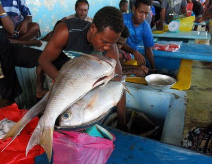 A man selling fish at Honiara's central market. Photo credit: Wikimedia.