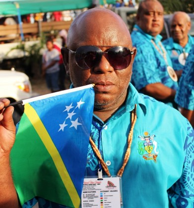 The late John Tahinao kisses the Solomon Islands Flag at the Festival opening ceremony on Saturday 28 June 2014. Photo credit: George Hermings.