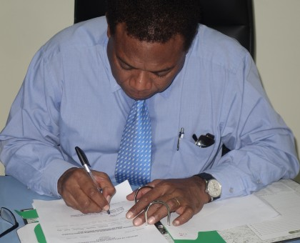 MEHRD Minister Dr Derek Sikua signing the release of the Form Six placement results. Photo credit: SIBC.