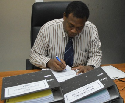 Minister of Education Dr Derek Sikua signing the 2015 school placement results. Photo credit: SIBC.