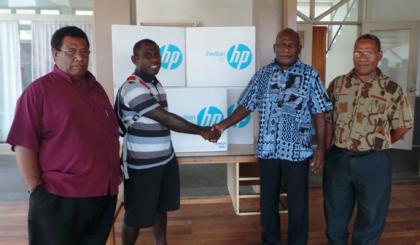 PS Ministry of Foreign Affairs Beraki Jino handing over the five computers to Su'u N.S.S Deputy Principle Colman Keniherea. Photo credit: GCU.