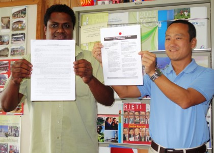 Japanese Embassy Administrative Officer Yasuyuki Nitta and a local staff displaying the scholarship papers. Photo credit : SIBC.