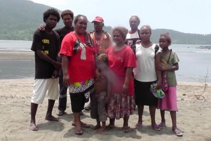 Fredrick Kusu and Elizabeth Sade, posing with villagers from Nariaoa, East Areare