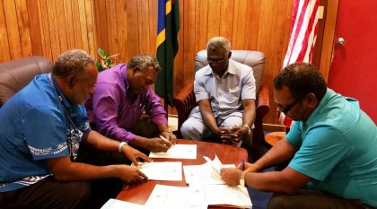 The MPs signing to the government as witnessed by Prime Minister Manasseh Sogavare. Photo credit: PM's Press Secretariat Office on Facebook.
