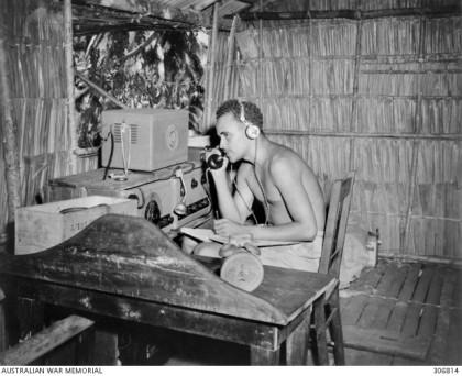 ) Sgt. William Bennett, MM, operating coastwatcher Teleradio station ZGJ5, New Georgia. (c. 1943) Credit: Australian War Memorial.