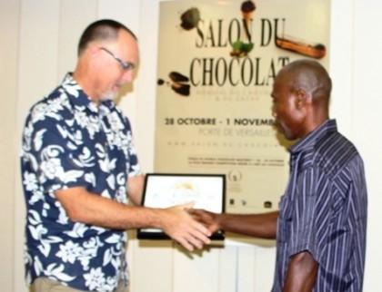 Australian High Commissioner Andrew Byrne hands the International Cocoa Award to David Kebu Junior. Photo credit: Australian High Commission Office.