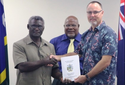 Prime Minister Manasseh Sogavare (L) receives the report from Australian High Commissioner Andrew Burne (R) in the presence of of Chairman of the Public Service Commission Elliam Tangirongo. Photo credit: GCU.