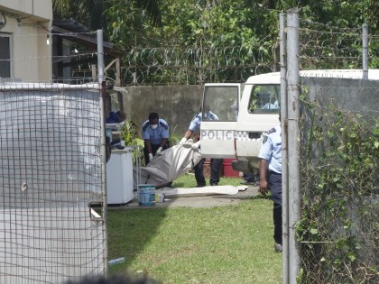 Police pull one of the bodies into the back of a police van