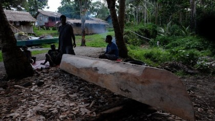A man in Kaogele village looks over the canoe he is making