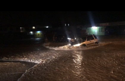A car plows through the flood water on Kukum Highway last night. It made it.