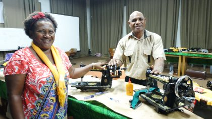 Couple stitching up sewing machine repair workshops